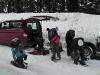 Gruppe vor einem Auto schnallt sich die Schneeschue an