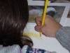 Kind zeichnet mit einem gelben Stift